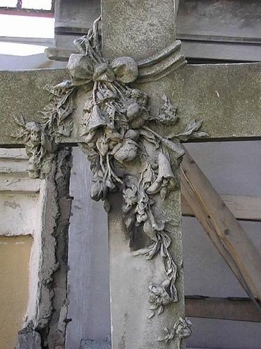 Черная корка и налеты биологического происхождения на кресте с гирляндой цветов.