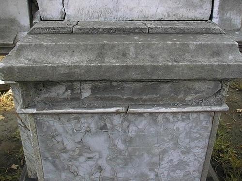 Трещины на постаменте из серого брекчиевидного мрамора.