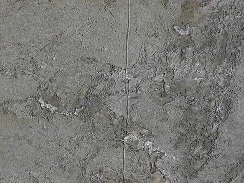 Трещина; углубления и впадины из-за выветривания на серо-зеленом мраморе.
