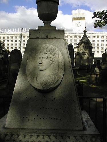 Углубления антропогенного происхождения на  обелиске из белого крупнозернистого мрамора с портретным барельефом.