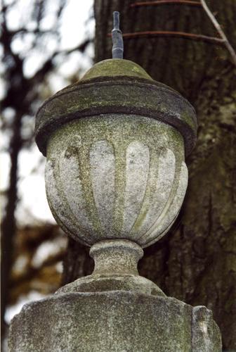 Урна из белого, мелко-, среднезернистого мрамора. Видно сильно проявленное отшелушивание, налеты биологического происхождения и атмосферные грязевые отложения. Фото ноября 2003 г.