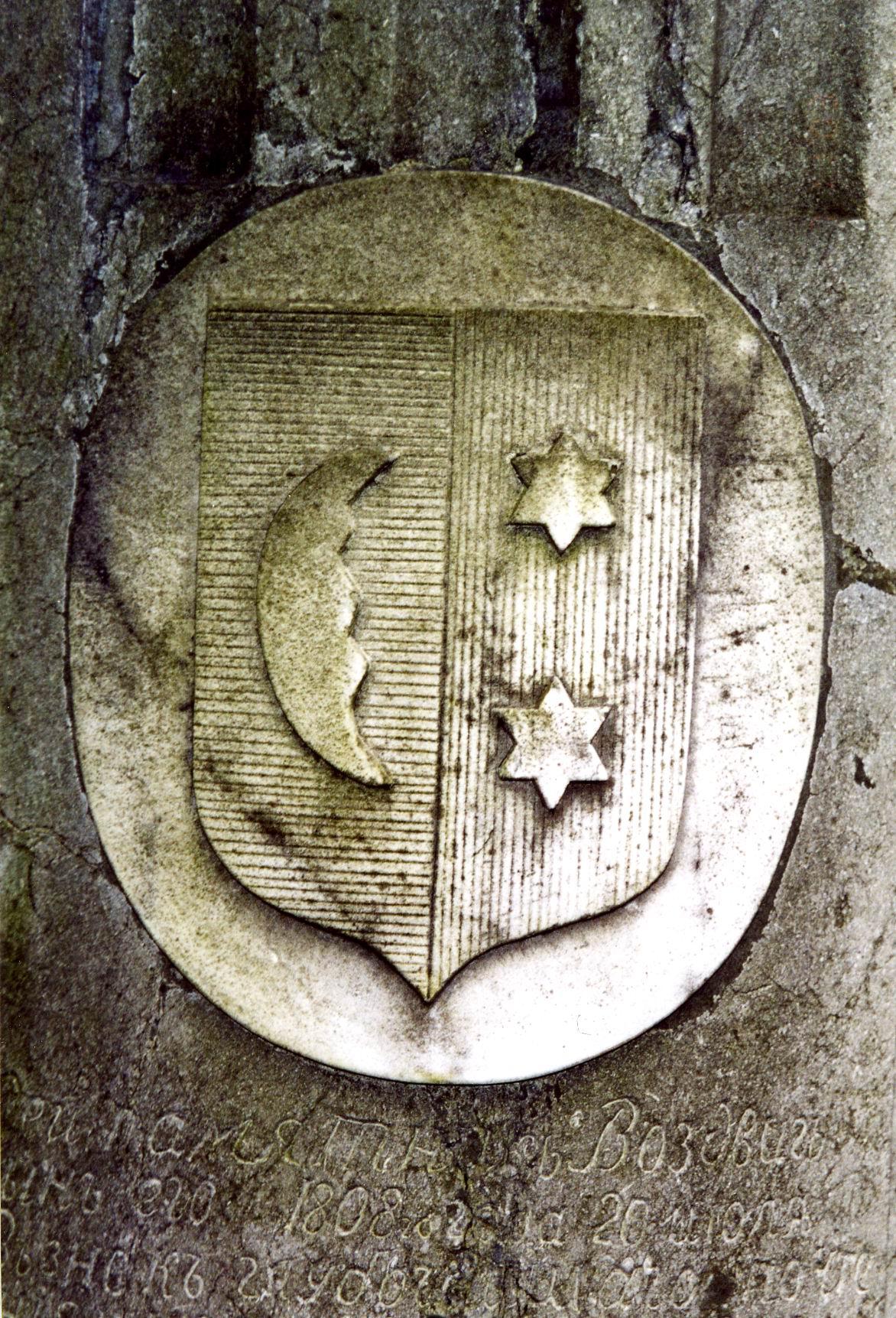 Западный герб из белого, мелко-, среднезернистого мрамора. Виден незначительный питтинг, колони водорослей и лишайников. Фото ноября 2003 г.