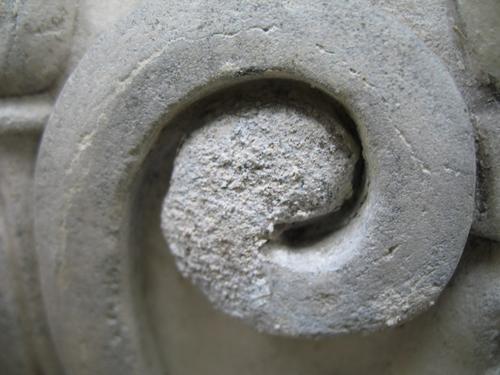 Выкрашивание камня и налет на поверхности рельефного завитка. Вероятно, солевое разрушение мрамора. Рельеф на саркофаге. Южная сторона памятника.