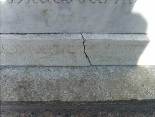 Трещины и бурые потеки на белом мраморе.