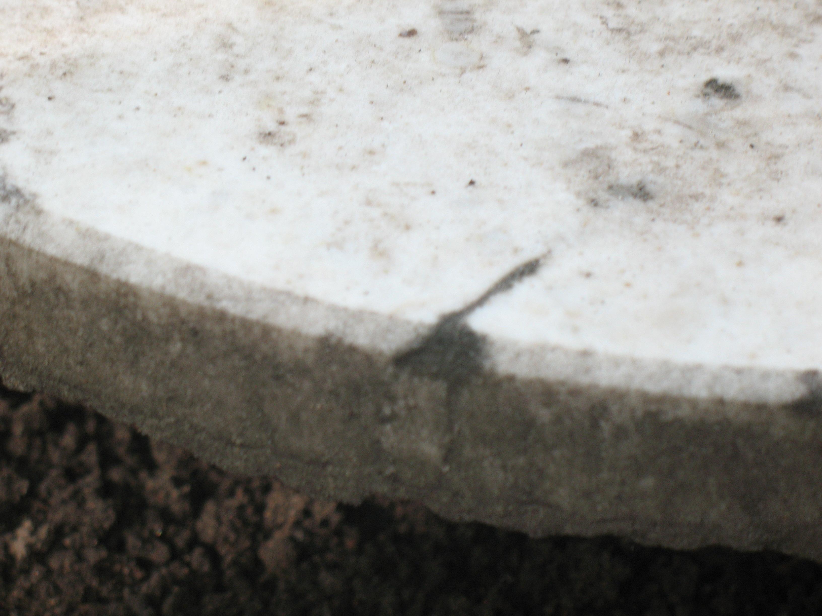 Выбоина неизвестного происхождения и грязевые наслоения на белом мраморе