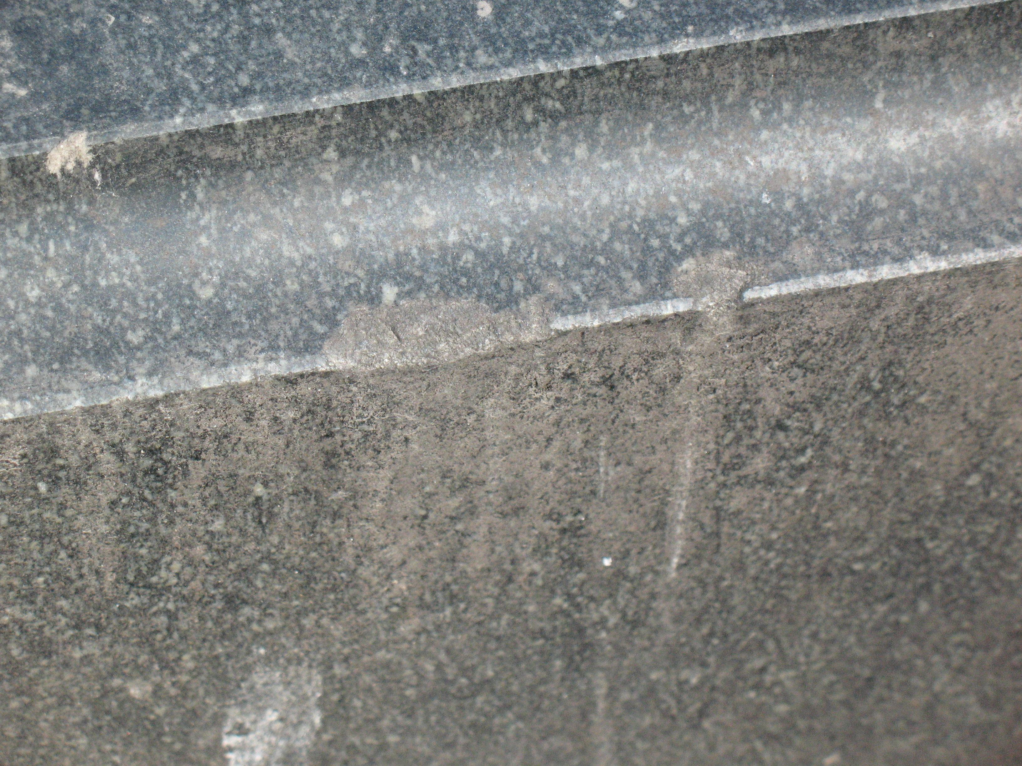 Углубления и впадины, атмосферные грязевые отложения на сером граните