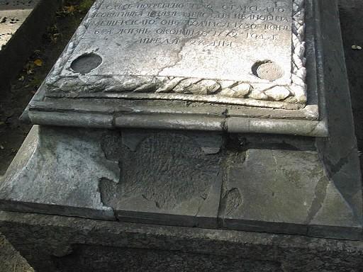 Нижняя плита саркофага из светло-серого, полосчатого, мелко-, среднезернистого мрамора. Видны налеты биологического происхождения, механические повреждения. Фото июля 2002 г.