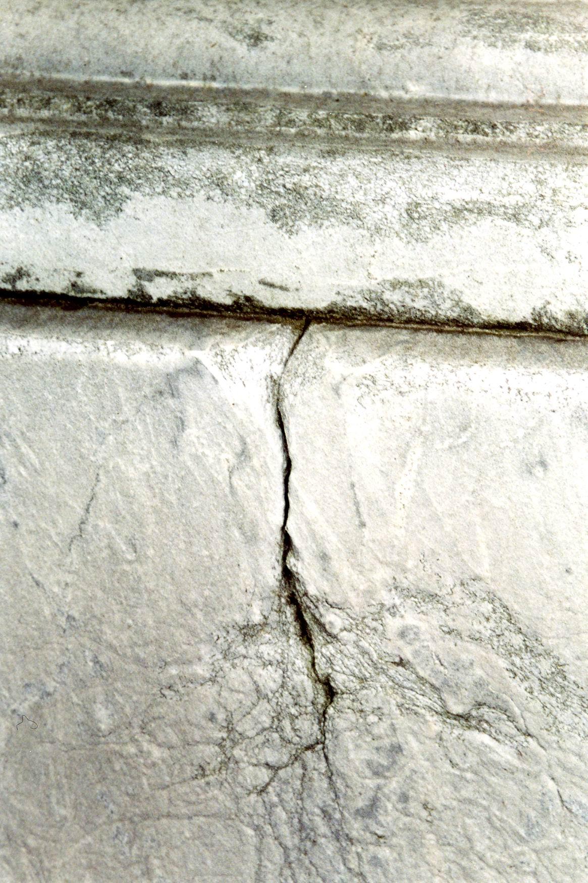 Фрагмент постамента. Южная сторона. Видно отшелушивание, трещина, приводящая к расколу г/п. Фото ноября 2003 г.
