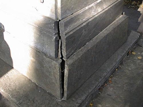 Расхождение нижних плит постамента из серого, полосчатого, мелко-, среднезернистого мрамора.