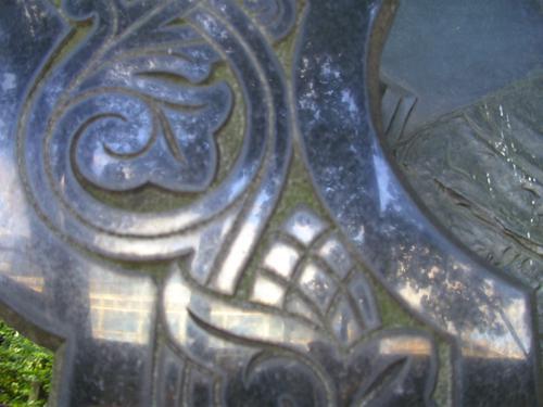 Биологигеские наслоения в резьбе на постаменте из черного габброида. Западная сторона постамента. Май 2011.