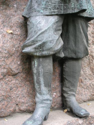 Неравномерное интенсивное развитие патины на поверхности  нижней части фигуры.