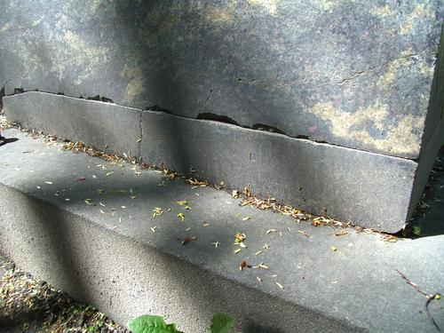 Трещины и сколы неизвестного происхождения на основании из темно-серого крупно-среднезернистого гранатового гнейсо-гранита. Южная сторона основания памятника. Май 2011.