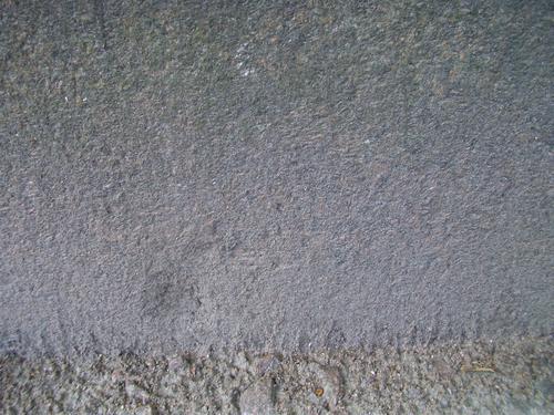 Грязевые наслоения на основании из красного мелко-среднезернистого гранита(вертекальная поверхность). Южная сторона основания.  Май 2011.