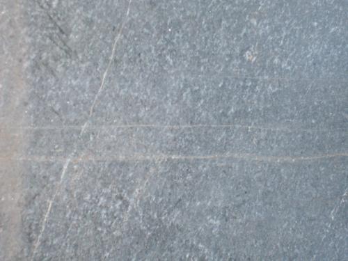 Трещины, атмосферные загрязнения на сером граните.