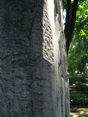 Скол неизвестного происхождения и грязевые отложения на постаменте из известняка. Северо-западная сторона постамента. Май 2011.