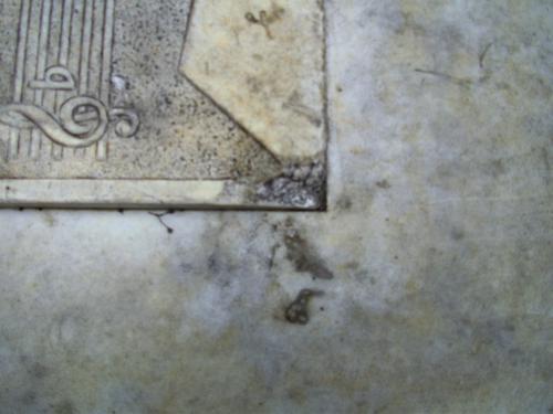 Грязевые наслоения и скол неизвестного происхождения на плите из белого однородного мрамора. Сентябрь 2011. Северная сторона плиты.