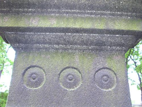 Биологический налёт и скол неизвестного происхождения на постаменте из чёрного мелкозернистого габброида. Северная сторона постамента. Май 2011.