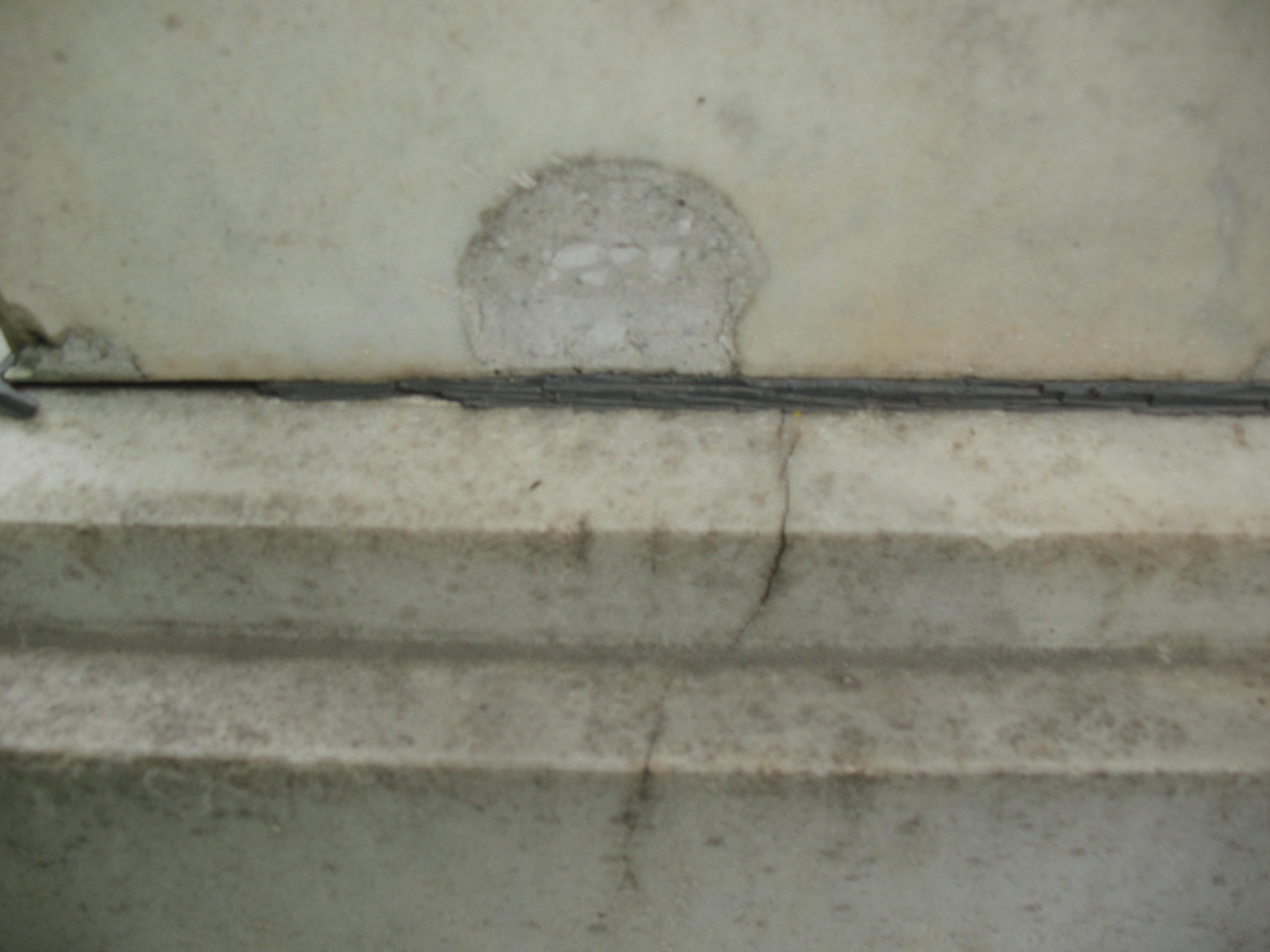 Выбоина неизвестного происхождения и трещина на белом мраморе