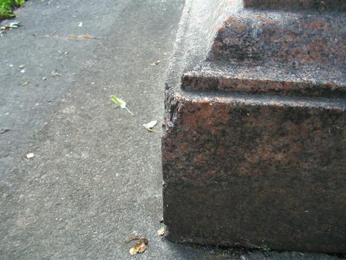 Скол неизвестного происхождения на углу постамента из красного гранита. Восточная сторона постамента. Май 2011.