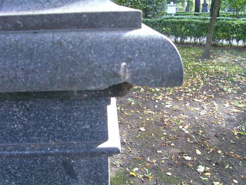 Скол неизвестного происхождения на постаменте из серого гнейсо- гарнита. Западная сторона постамента. Май 2011
