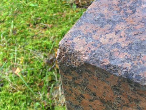 Скол неизвестного происхождения на фундаменте из красного порфировидного гранита. Юго-восточная сторона фундамента. Май 2011.