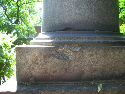 2 скола неизвестного происхождения на колонее и основании колонны из серого гранита. Западная сторона колонны. Май 2011