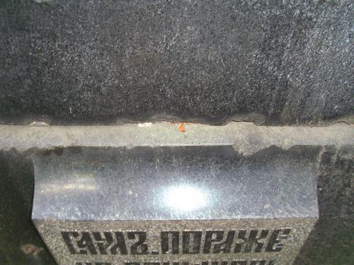 Сколы неизвестного происхождения на постаменте из серго гнейсо-гранита. Восточная сторона постамента. Май 2011.