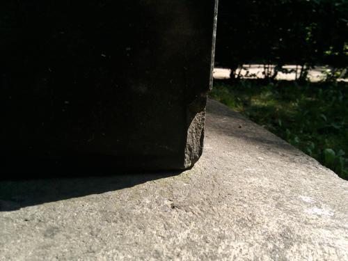 Скол неизвестного происхождения на плите из мелкозернистого чёрного габбоида. Северо-западный угол плиты. Май 2011.
