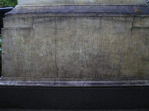 Грязевые наслоения, выкрашивание и множество трещин на фундаменте памятника из белого однородного мрамора. Восточная сторона памятника. Сентябрь 2011.