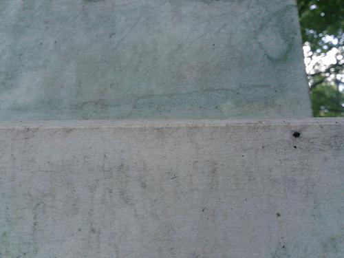 Мелкие трещины и потёк от бронзы на белом мелко-среднезернистом однородном мраморе. Северная сторона постамента. Сентябрь 2011 г.