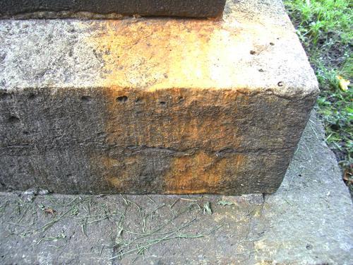 Расслаивание фундамента из серого плитчатого известняка и потёки неизвестного происхождения. Восточная сторона фундамента. Май 2011.