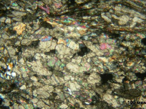 Микрофотография шлифа желтовато-белого мраморизованного известняка; николи + Порода сложена преимущественно изометричными зёрнами кальцита, величиной 0,2-0,4мм. Отдельные участки представляют собой неравномернозернистые агрегаты, где кальцит образует как изометричные зёрна величиной 0,1-0,8мм, так и шестоватые кристаллы. В этих участках отмечаются также слюдистые агрегаты, часто деформированные. В межзерновом пространстве наблюдаются редкие мелкие зёрна кварца.