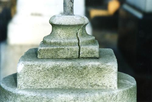 Ножка урны из белого, мелко-,среднезернистого мрамора. Видны трещина,приводящая к раскалыванию г/п, отшелушивание, налеты биологического происхождения и атмосферные грязевые отложения. Фото ноября 2003 г.