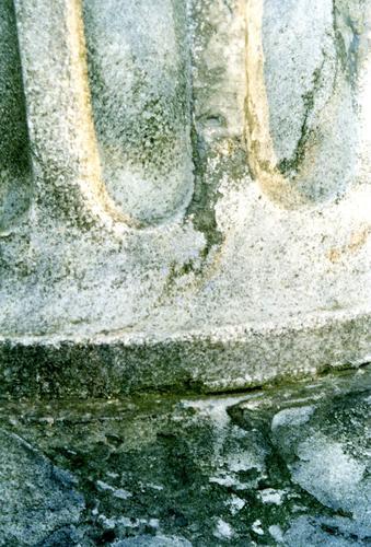 Фрагмент подставки для нижней полуколонны из серого, полосчатого, узорчатого, мелко-, среднезернистого мрамора. Видны налеты биологического происхождения. Фото ноября 2003 г.