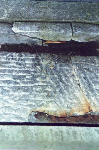 Нижняя часть стелы из серого, полосчатого, мелко-, среднезернистого мрамора. Южная сторона. Видны механические повреждения, отшелушивание. Фото ноября 2003 г.