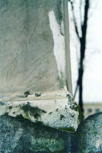 Нижняя часть обелиска. Северная сторона. Видно отслаивание мрамора, отшелушивание. Фото ноября 2003 г. Стрелкой указано место взятия образца.