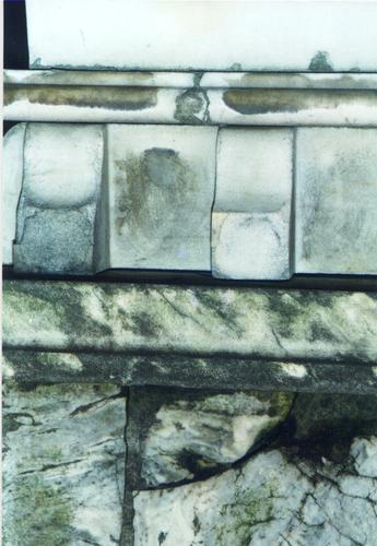 Верхняя часть пилона из белого, мелко-, среднезернистого мрамора. Северная сторона. Видно начало образования черной корки, биологический налет, трещины. Фото ноября 2003 г.