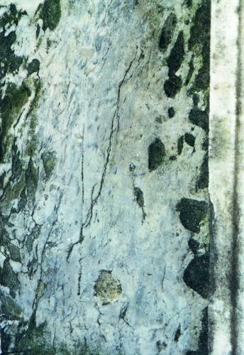 Верхняя часть пилона из серого, тонкополосчатого, мелко-, среднезернистого мрамора. Западная сторона. Видны микротрещины, налет биологического происхождения. Фото ноября 2003 г.