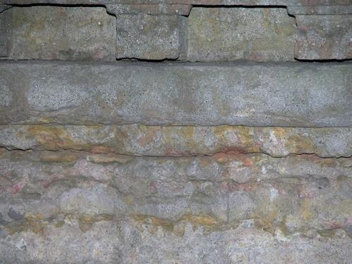Фрагмент саркофага из путиловского известняка. Видны углубления и впадины из-за выветривания, начало образования черной гипсовой корки. Фото ноября 2003 г.